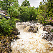 Betws-y-Coed Afon Llugwy Rapids Snowdonia. The Afon Llugwy (River Llugwy) rapids flowing through Betws-y-Coed after particularly heavy rainfall. Betws-y-Coed is a small village in the heart of the Snowdonia National Park that is a popular base for hikers.