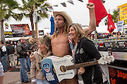 The Naked Cowboy from New York's Time Square poses with women during a visit to the 74th Annual Daytona Bike Week March 7, 2015 in Daytona Beach, Florida.