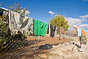 24 JANUARY 2010 -- WENDEN, AZ:  Leopoldo Portugal (CQ) cleans up the yard of his home, while his clothes dry on his fence, in Wenden. Wenden was slammed by its second 100 year flood in 10 years on Thursday night when water raced through Centennial Wash and into the small town in La Paz County west of Phoenix. Most of the town's residents were evacuated to Red Cross shelters in Salome, about 5 miles west of Wenden.   PHOTO BY JACK KURTZ