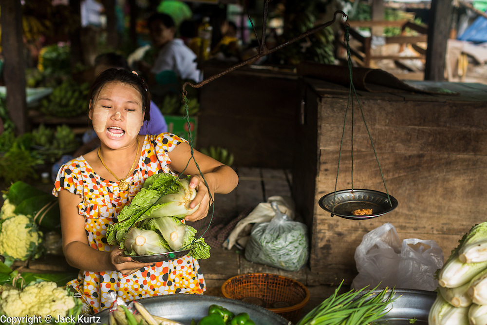 06 JUNE 2014 - IRRAWADDY DELTA,  AYEYARWADY REGION, MYANMAR: A woman weighs leaf lettuce for a customer in the market in Pantanaw, a town in the Irrawaddy Delta (or Ayeyarwady Delta) in Myanmar. The region is Myanmar's largest rice producer, so its infrastructure of road transportation has been greatly developed during the 1990s and 2000s. Two thirds of the total arable land is under rice cultivation with a yield of about 2,000-2,500 kg per hectare. FIshing and aquaculture are also important economically. Because of the number of rivers and canals that crisscross the Delta, steamship service is widely available.   PHOTO BY JACK KURTZ