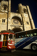 A chaotic scene on the streets of the Portuguese capital as an old tram clashes with a modern tourist coach below the towering Se Cathedral in central Lisbon. Passing very close to each other, fighting for space on the old winding streets, different modes of transport rumble by, competing for the streets below this Lisbon landmark. The Patriarchal Cathedral of St. Mary Major is a Roman Catholic parish church located in Lisbon, Portugal. The oldest church in the city is the see of the Archdiocese of Lisbon. Since the beginning of the construction of the cathedral, in the year 1147, the building has been modified several times and survived many earthquakes.