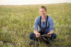 "Bird Researcher Marisa Lipsey poses at The Nature Conservancy's Matador Ranch in Eastern Montana. The ""grass bank"" is an innovative way to leverage conservation gains, in which ranchers can graze their cattle at discounted rates on Conservancy land in exchange for improving conservation practices on their own ""home"" ranches. In 2002, the <br /> Conservancy began leasing parts of the ranch to neighboring ranchers who were suffering from  severe drought, offering the Matador's grass to neighboring ranches in exchange for their  participation in conservation efforts. The grassbank has helped keep ranchers from plowing up native grassland to farm it; helped remove obstacles to pronghorn antelope migration; improved habitat for the Greater Sage-Grouse and reduced the risk of Sage-Grouse colliding with fences; preserved prairie dog towns and prevented the spread of noxious weeds. (Photo By Ami Vitale)"