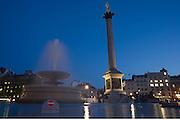 In late evening light, fountain spray drifts across Trafalgar Square  beneath Nelson's Column.