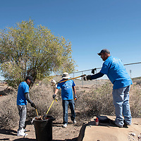 Left to right, Comcast employees Fonz Benally, Reynaldo Brown and John Ortiz, volunteer at the Comcast Cares Community Cleanup Day by picking up trash on 9th Street, Saturday, May 4 in Gallup.