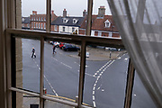 An evening viewpoint through a sash window of two pedestrians walking next to a  road junction and a market place of closed shop businesses in a rural Norfolk town, on 30th June 2021, in Aylsham, Norfolk, England.