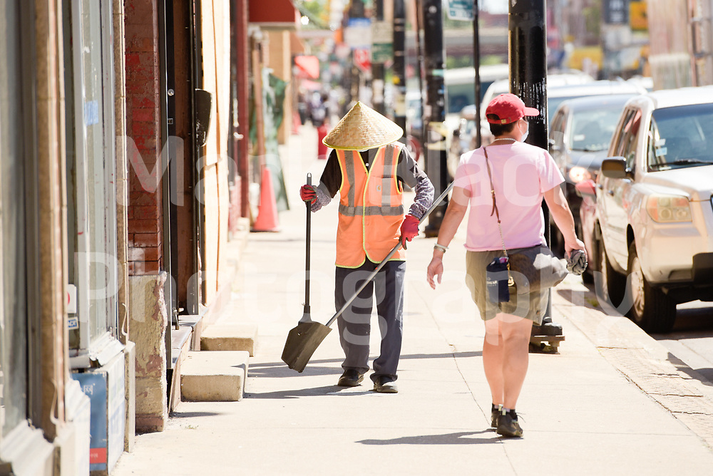 A man wearing a Asian conical hat, commonly known as an Asian rice hat sweeps the sidewalk of Chicago's Chinatown on Wednesday, Aug. 19, 2020.  Photo by Mark Black