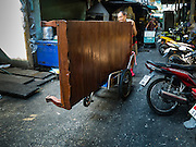 04 JANUARY 2016 - BANGKOK, THAILAND:  A vendor moves his daybed out of his stall in Bang Chak Market after the market closed permanently. The market closed January 4, 2016. The Bang Chak Market serves the community around Sois 91-97 on Sukhumvit Road in the Bangkok suburbs. About half of the market has been torn down. Bangkok city authorities put up notices in late November that the market would be closed by January 1, 2016 and redevelopment would start shortly after that. Market vendors said condominiums are being built on the land.       PHOTO BY JACK KURTZ