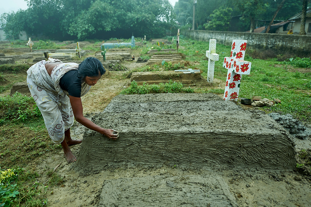 In preparation for All Souls Day, Lochina Murmu repairs a grave in the Christian cemetery in Suihari in northern Bangladesh.