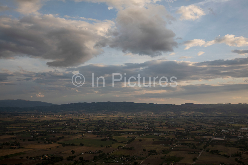 View over the valley south of Assisi, Umbria, Italy. Assisi is a town in the Province of Perugia in the Umbria region, on the western flank of Monte Subasio. It is generally regarded as the birthplace of the Latin poet Propertius, and is the birthplace of St. Francis, who founded the Franciscan religious order in the town in 1208, and St. Clare, Chiara dOffreducci, the founder of the Poor Sisters, which later became the Order of Poor Clares after her death. Assisi is now a major tourist destination for those sightseeing or for more religious reasons.