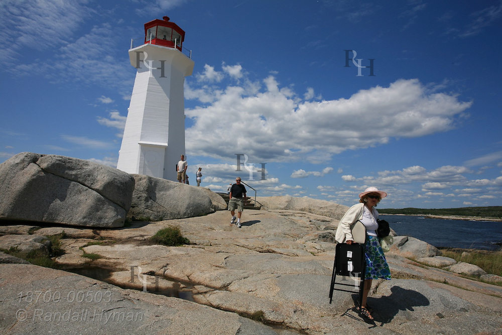 Tourists visit the classic lighthouse (built 1914) and slab granite shore of Peggys Point outside the village of Peggys Cove, Nova Scotia, Canada.