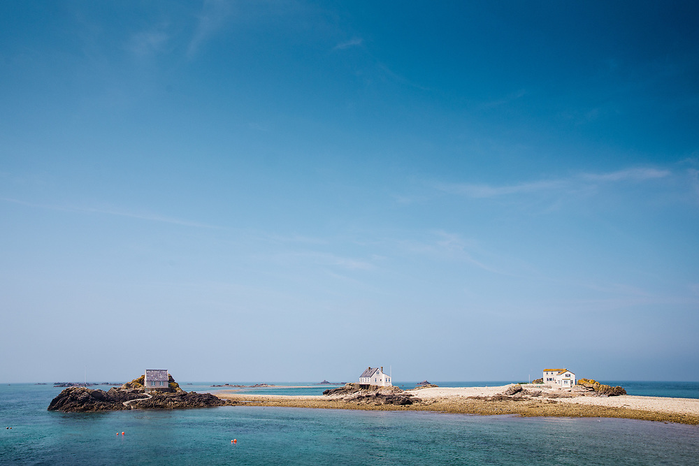 The houses, rocks, pebbly beach and sandbanks at the Ecrehous, a popular day trip on a boat from Jersey, Channel Islands