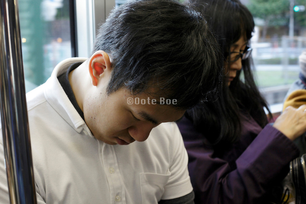 making a day nap during the train commute Japan Tokyo