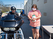 "26 APRIL 2020 - JEWELL, IOWA: MISCHELLE HARDY, talks to a motorcyclist who bought ""grab and go"" roast pork dinners in Jewell during a fund raiser Sunday. Jewell, a small community in central Iowa, became a food desert when the only grocery store in town closed in 2019. It served four communities within a 20 mile radius of Jewell. Some of the town's residents are trying to reopen the store, they are selling shares to form a co-op, and they hold regular fund raisers. Sunday, they served 550 ""grab and go"" pork roast dinners. They charged a free will donation for the dinners. Despite the state wide restriction on large gatherings because of the COVID-19 pandemic, the event drew hundreds of people, who stayed in their cars while volunteers wearing masks collected money and brought food out to them. Organizers say they've raised about $180,000 of their $225,000 goal and they hope to open the new grocery store before summer.          PHOTO BY JACK KURTZ"