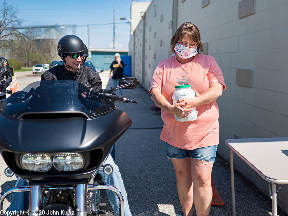 """26 APRIL 2020 - JEWELL, IOWA: MISCHELLE HARDY, talks to a motorcyclist who bought """"grab and go"""" roast pork dinners in Jewell during a fund raiser Sunday. Jewell, a small community in central Iowa, became a food desert when the only grocery store in town closed in 2019. It served four communities within a 20 mile radius of Jewell. Some of the town's residents are trying to reopen the store, they are selling shares to form a co-op, and they hold regular fund raisers. Sunday, they served 550 """"grab and go"""" pork roast dinners. They charged a free will donation for the dinners. Despite the state wide restriction on large gatherings because of the COVID-19 pandemic, the event drew hundreds of people, who stayed in their cars while volunteers wearing masks collected money and brought food out to them. Organizers say they've raised about $180,000 of their $225,000 goal and they hope to open the new grocery store before summer.          PHOTO BY JACK KURTZ"""