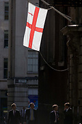 The flag of the City of London hangs in sunlight over gentlemen in the City of London, England UK. Four young man walk along this narrow lane, passing below the flag that represents the capital's financial district also called the Square Mile, the oldest quarter of London, founded by the Romans in AD43. The flag of the City of London is based on the flag of England, having a centred red St George's Cross on a white background, with the red sword in the upper hoist canton (the top left quarter). The City is only a tiny part of the metropolis of Greater London, though it remains a notable part of central London. It holds city status in its own right and is also a separate ceremonial county.