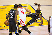 Golden State Warriors forward Kevon Looney (5) is knocked down by Houston Rockets guard Eric Gordon (10) during Game 4 of the Western Conference Finals at Oracle Arena in Oakland, Calif., on May 22, 2018. (Stan Olszewski/Special to S.F. Examiner)