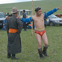 A nomadic herder prepares to wrestle at a naadam festival on a remote pass near Muren, Mongolia. This ancient sport is immensely popular across the country, and legend says that men wear their unique costumes to prove that they are not women, after an early empress humiliated her warriors by beating them. Here the competitor is mimicking a bird, a traditional ritual.