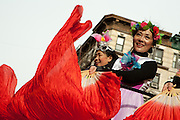 Women in traditional costumes wave red banners from a float.
