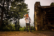 A guitar and gun maker stands with his guitar over his shoulder next to an old cabin in the mountains of North Carolina.