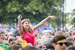 © Licensed to London News Pictures . 20/07/2013 . Suffolk , UK . A woman dances amongst the crowd surrounded by bubbles as Jessie Ware performs on the Obelisk Stage . The Latitude music and culture festival in Henham Park , Southwold . Photo credit : Joel Goodman/LNP