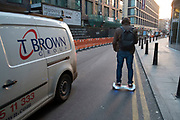 Man commuting on his hoverboard passes other traffic going in the opposite direction. London, England, UK. A self-balancing two-wheeled board, or self-balancing electric scooter, also commonly referred to as a hoverboard, is a type of portable, rechargeable battery-powered scooter. They typically consist of two wheels arranged side-by-side, with two small platforms between the wheels, on which the rider stands. The device is controlled by the rider's feet, standing on the built-in gyroscopic, sensored pads.