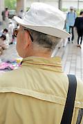 elderly man wearing a little white hat seen from the back