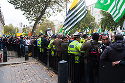 Trafalgar Square, London, October 26th 2014. Thousands of Kashmiris in London demonstrate in Trafalgar Square before marching to Downing Street to deliver a petition asking for Britain's support in ending the occupation of Kashmir by India. PICTURED: Police stuggle against the weight of the crowd outside Downing Street.