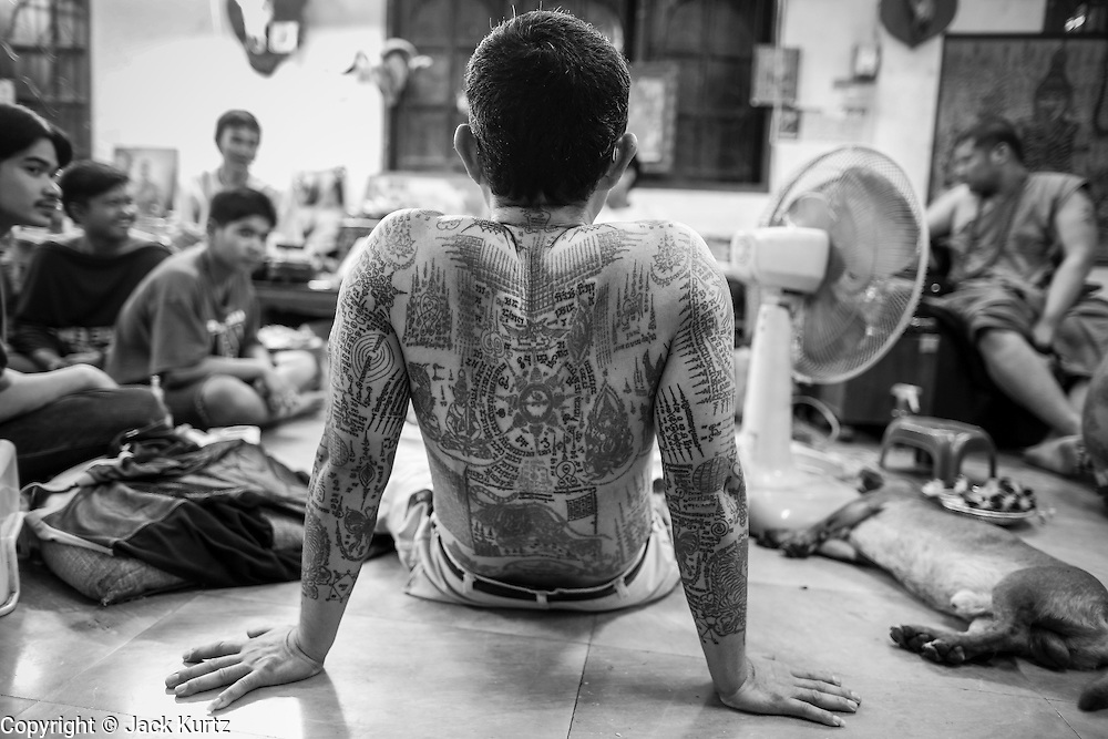 """14 MARCH 2014 - NAKHON CHAI SI, NAKHON PATHOM, THAILAND: A man relaxes between sessions to refresh his sak yant tattoo at Wat Bang Phra. Wat Bang Phra is the best known """"Sak Yant"""" tattoo temple in Thailand. It's located in Nakhon Pathom province, about 40 miles from Bangkok. The tattoos are given with hollow stainless steel needles and are thought to possess magical powers of protection. The tattoos, which are given by Buddhist monks, are popular with soldiers, policeman and gangsters, people who generally live in harm's way. The tattoo must be activated to remain powerful and the annual Wai Khru Ceremony (tattoo festival) at the temple draws thousands of devotees who come to the temple to activate or renew the tattoos. People go into trance like states and then assume the personality of their tattoo, so people with tiger tattoos assume the personality of a tiger, people with monkey tattoos take on the personality of a monkey and so on. In recent years the tattoo festival has become popular with tourists who make the trip to Nakorn Pathom province to see a side of """"exotic"""" Thailand.   PHOTO BY JACK KURTZ"""