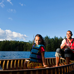 A man, woman, and young girl canoe on Zack Woods Pond in Hyde Park, Vermont. Green River Reservoir State Park