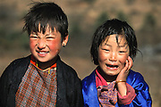 Young girls in Jakar Village, east central Bhutan, are wearing the female Bhutanese national dress, called a kira, with a traditional over-jacket. The King of Bhutan has decreed that adults must wear the country's traditional dress.  From coverage of revisit to Material World Project family in Bhutan, 2001. .