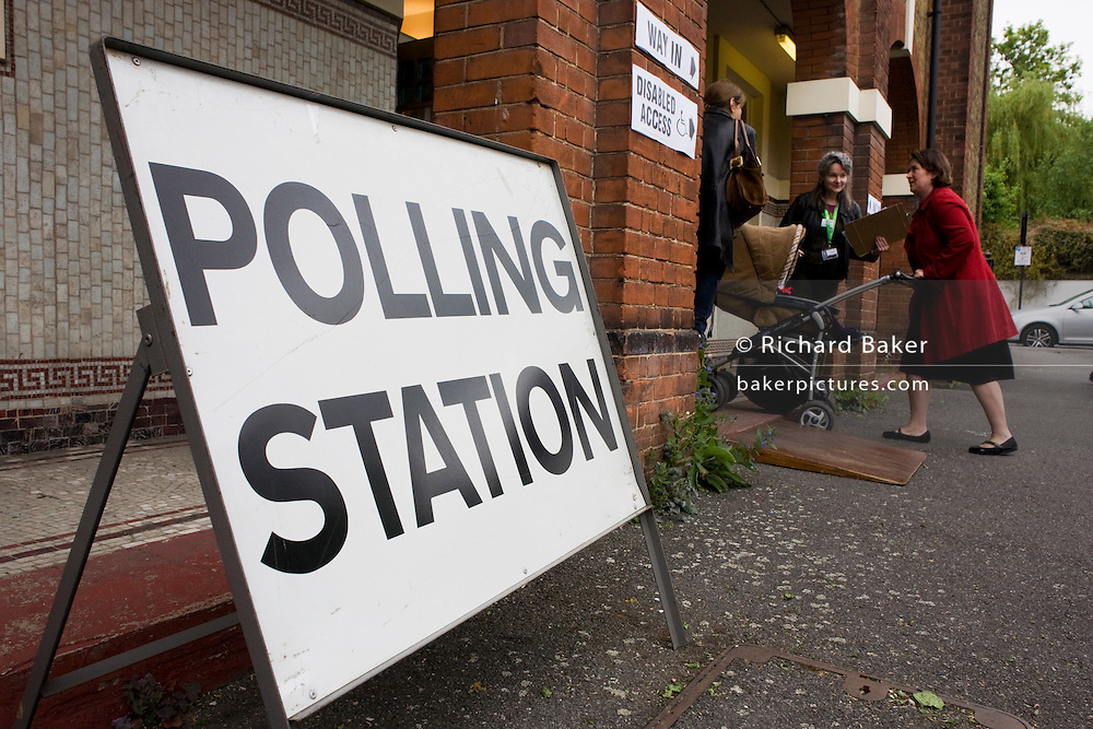 A mother pushes her child into St. Saviour's Church, Herne Hill SE24 in south London that serves as a temporary Polling station for voters on Britain's general election day.