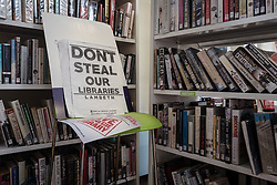 © Licensed to London News Pictures. 01/04/2016. London, UK. A placard left next to a bookshelf in Herne Hill's Carnegie Library, which is currently occupied by local residents in an effort to prevent its closure. Lambeth Council had planned to close the library last night (31st March) in order to turn it into a 'healthy living centre'. Photo credit : Rob Pinney/LNP
