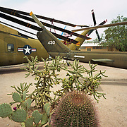 Two US Navy helicopters have been parked next to some cacti at the Pima Air and Space Museum near Davis Monthan Air Force base, Tucson, Arizona. In the arid desert heat we see only the rear sections of the aircraft, their rotors have been moved into a storage position and so echo the arm-like form and camouflaged tones of the cactus branches. The ground is sandy from the desert floor and soft, overhead light casts a shadow beneath the aircraft's fuselage. Picture from the 'Plane Pictures' project, a celebration of aviation aesthetics and flying culture, 100 years after the Wright brothers first 12 seconds/120 feet powered flight at Kitty Hawk,1903.