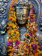 A buddha decorated with marigolds and other flowers, at the Golden Temple, (Hiranya Varna, or Suwarna Mahavihara), a Buddhist Monastery existing since 1409 or earlier, located just north of Durbar Square in Patan, Nepal.
