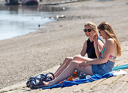 © Licensed to London News Pictures. 07/08/2020. London, UK. Two sunbathers enjoy the sunshine next to the River Thames at Putney Embankment in South West London as temperatures are expected to reach to 35c today. Thousands of sun seekers have flocked to parks, rivers and the south coast as temperatures soar with beaches and roads becoming jammed with holidaymakers. The heat is set to continue for the rest of the week with temperatures expected in the high 20s. Photo credit: Alex Lentati/LNP