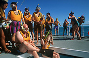 A group of cruise ship passengers prepare for a morning scuba diving in the blue waters off Cancun, Gulf of Mexico. Having left their ship for a few hours excursion into the warm tropical sea, the men and women ready themselves before submerging below the floating platform. With masks and snorkels already in place, they take turns to sit on a step and take the plunge. Many look unfit and unused to diving – especially the fatter, older man in the foreground. But for many this holiday is a trip of a lifetime so they won't want to miss such an opportunity. The skies are blue and they are miles from land and the worries of work and home. They are here for adventure and have the money to make it happen.