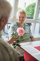 Senior man giving rose to woman at rest home, Bavaria, Germany, Europe
