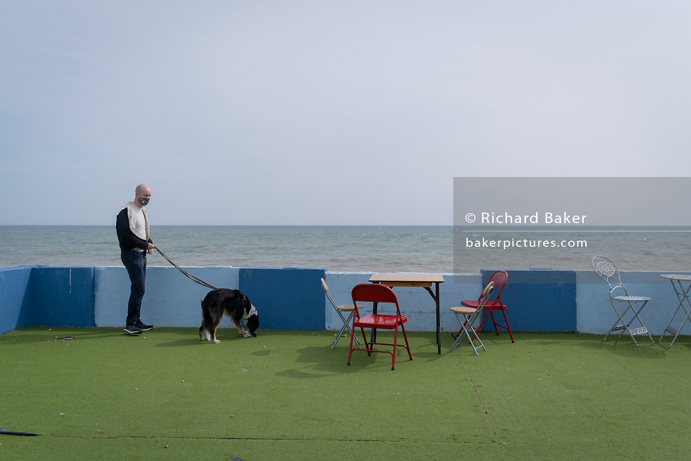 A pet owner and his dog at the outdoor seafront cafe that was once a part of the St Leonards Bathing pool (opened 1933), on 3rd May 2021, in St Leonards, Sussex, England.