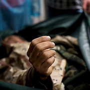 Nurses at Benghazi's hospital morgue cover the body of a rebel fighter killed during clashes with Gaddafi's forces in the outskirts of the city.
