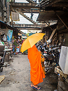 24 FEBRUARY 2015 - PHNOM PENH, CAMBODIA: A Buddhist monk walks into the White Building. The White Building, the first modern apartment building in Phnom Penh, originally had 468 apartments, and was opened the early 1960s. The project was overseen by Vann Molyvann, the first Cambodian architect educated in France. The building was abandoned during the Khmer Rouge occupation. After the Khmer Rouge were expelled from Phnom Penh in 1979, artists and dancers moved into the White Building. Now about 2,500 people, mostly urban and working poor, live in the building. Ownership of the building is in dispute. No single entity owns the building, some units are owned by their occupants, others units are owned by companies who lease out apartments. Many of the original apartments have been subdivided since the building opened and serve as homes to two or three families. The building has not been renovated since the early 1970s and is in disrepair. Phnom Penh officials have tried to evict the tenants and demolish the building but residents refuse to move out.   PHOTO BY JACK KURTZ