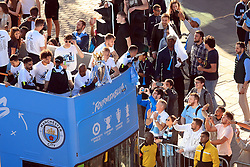 Manchester City's Fabian Delph and Oleksandr Zinchenko with the Premier League trophy on the bus as they pass the crowds of fans gathered on the route during the trophy parade in Manchester.