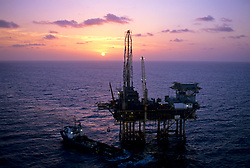 Stock photo of a jack up drilling rig with a pilot boat