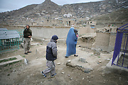 Marzia, 46, the first wife of Noor Agha, at right, takes her youngest child, Alisa, 2, to a doctor, Kabul, Afghanistan, Thursday, March, 8, 2007. Noor Agha is a renowned kite maker who made kites for the movie makers of the best-selling novel, The Kite Runner, which will be distributed by Dreamworks and Paramount Vantage in Nov. this year. Noor Agha's wives, using their special glue, help him produce enough kites to please the clients' needs. Some of his children can also make their own kites with plastic bags and bamboo sticks. As the Afghan New Year's Day (Nawruz) approaching on March 21, the finger tips of Noor Agha's family got busier for mass production.