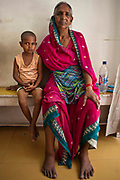 A young Indian girl sitting with her grandmother inside a health clinic waiting to be seen by a healthcare professional in Tehkhand Slum, Delhi, India.