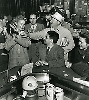 1945 Sidney Skolsky (sitting at the counter) and Jack Oakie (reaching for the skunk) admiring the skunk at Schwab's Pharmacy