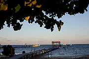 Caye Caulker island ocean view, boats and jetee at dusk, Belize.
