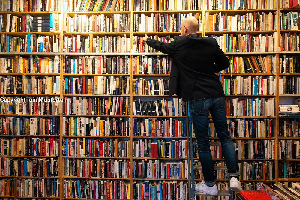 Customer browsing for second hand books in St George's book shop in Prenzlauer Berg , Berlin, Germany