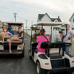 August 4, 2017 - Tangier Island, VA - A deep sense of community informs the citizens of Tangier Island who often stop in the roadway to chat in afternoons after the days work on the water is done.  Few cars are on the small island, but almost every house has a golf cart parked in front of it for easy transportation.<br /> <br /> Photo by Susana Raab/Institute