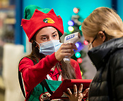 Sharon Bonilla, one of Santa's helpers, takes temperature scans as families arrive to meet Santa Claus on Tuesday, Nov. 24, 2020 at Bass Pro Shops in Gurnee. (Brian Cassella/Chicago Tribune)