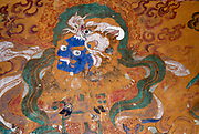 Ancient mural painting of a blue faced  demon. The demon has a makara, a water monster as a hat .  Tamshing Goemba, Bumthang, Bhutan, Drul Yul. 16 November 2007